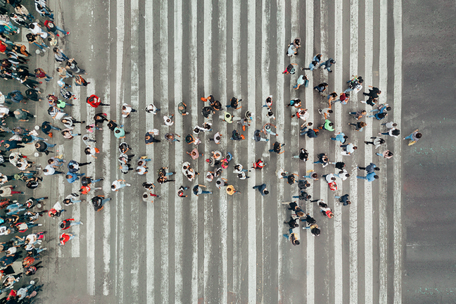 Aerial view of pedestrians walking in the formation of an arrow pointing forward.