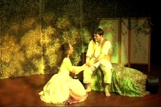 The characters of Musella and Phillisses hold hands in the forest