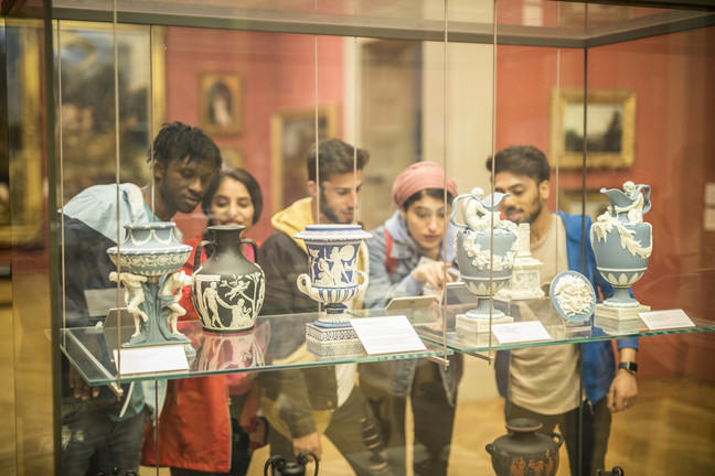5 students standing in a museum looking at artefacts in a glass cabinets