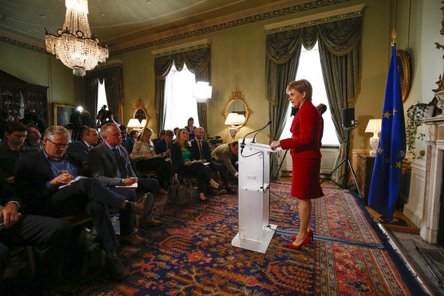 Scotland First Minister Nicola Sturgeon standing and speaking at a podium on the right towards an audience of journalists on the left