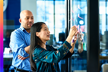 Business Woman sticking notes on glass with colleague