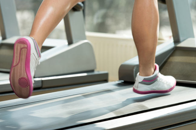 A pair of legs running on a treadmill with pink and white shoes.