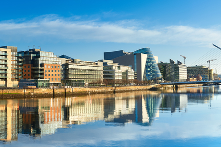 A sunny morning in Dublin looking out onto the Docklands and the Samuel Beckett Bridge from the Liffey. The cityscape is reflected in the water.