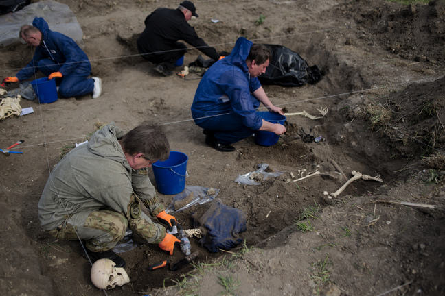 People excavating some mock burials as part of a training course in forensic archaeology. The cast skeletons are partially exposed