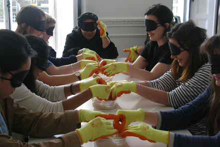 Decorative image, people taking part in a practical exercise wearing blindfolds and gloves to feel substrate in a box. Celebrating Neurodiversity. AcrossRCA 2014