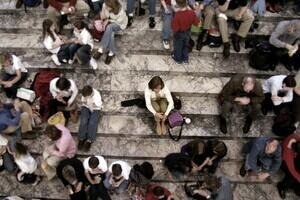 A woman sits on her own, isolated, on a flight of stairs surrounded by a large crowd of people.