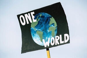 Placard showing the earth and the words 'one world'.