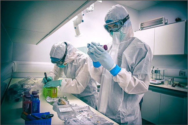 Two scientists prepare DNA samples in a lab. They are both wearing white coveralls and masks to prevent contamination.
