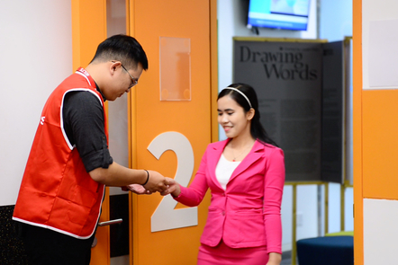 A student arriving at the IELTS test room and handing over her ID