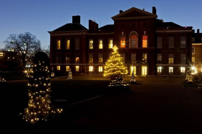A landscape photograph of Kensington Palace at night, illuminated by trees with Christmas lights