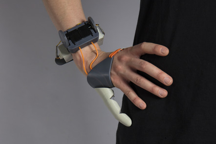 Decorative image, hand wearing a mechanical device that gives the wearer an extra finger or thumb for increased mobility. By Dani Clode, The Third Thumb.