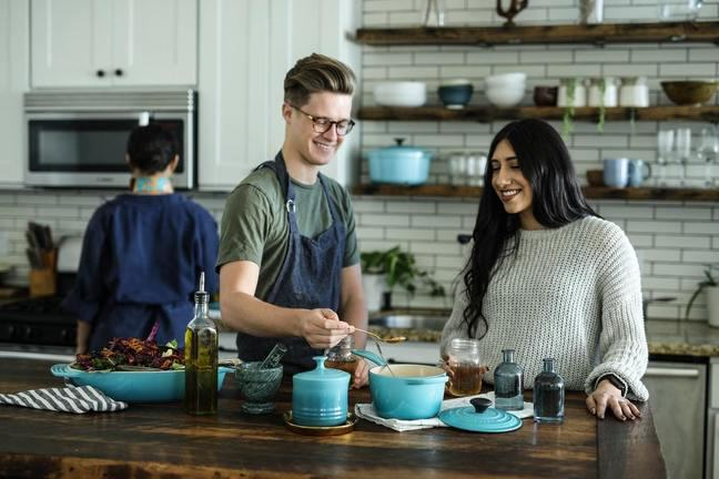 a smiling man wearnig an apron, standing near a smiling woman in a kitchen. Both are looking at a cooking pot.