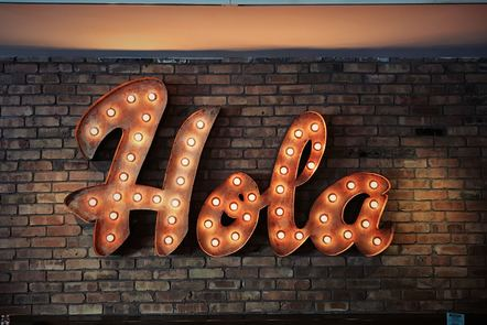 A sign lit up with light bulbs, which says 'Hola'.