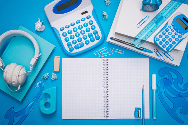Open spiral notebook with stationery and headphones on light blue background