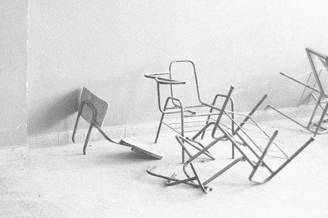 Black and white image of broken desks in an abandoned classroom