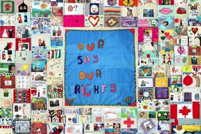 A quilt with 'Our say, our rights' sewed on the front.