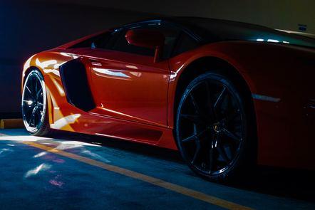 Rays of light hitting an orange sports car in shadow