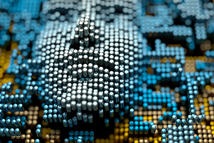 Abstract image of a human face emerging from a landscape of metallic cylinders.