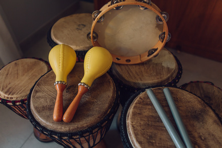A collection of percussion instruments including drums, a tambourine, maracas and drumsticks