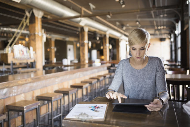 Woman deciphering figures in industrial restaurant venue