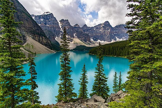 Image of turquoise lake with mountains in the background.