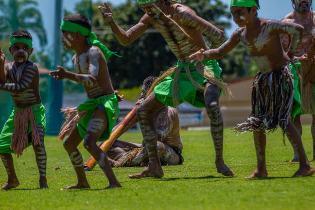 A group of young Aboriginal boys, dressed in traditional costume are dancing on the grass.
