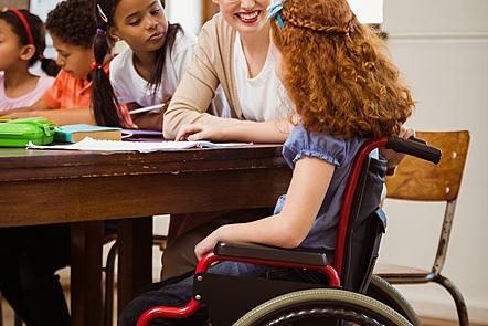 Teacher at a desk with pupils
