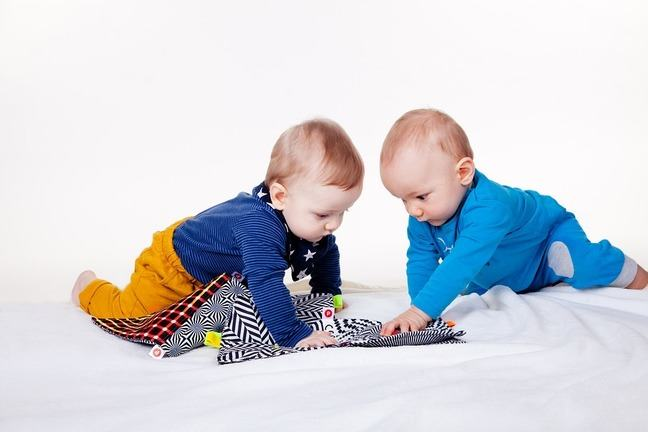 Two babies over a bedspread