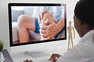 A physiotherapist sitting in front of a computer, viewing an image of a patient holding his knee in pain.