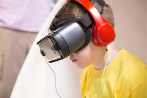 A photograph of a boy using a virtual reality headset and headphones