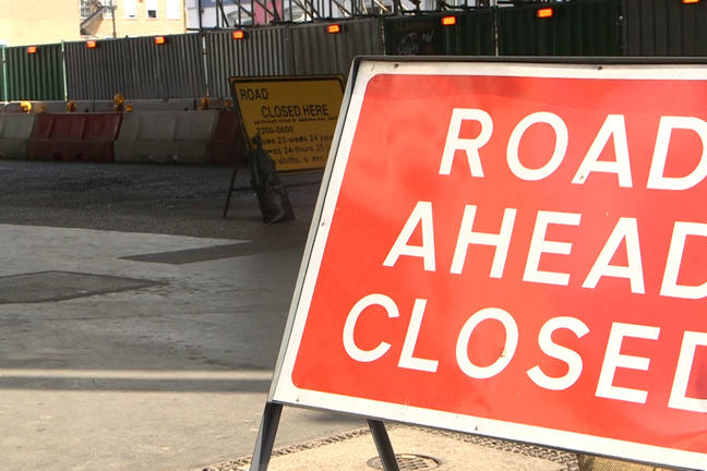 'Road ahead closed' signs blocking off a city street.