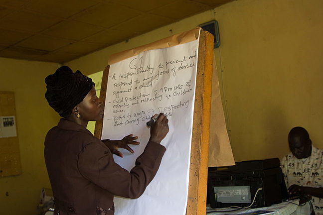 African woman writes goals and plans on a flipchart