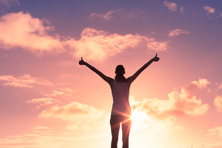 A woman standing in front of a beautiful sunset giving two thumbs up.
