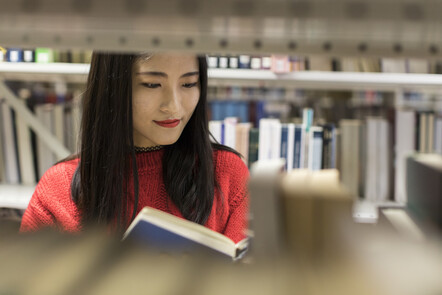 Student looking for books in the library