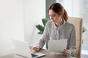 A women holding some papers and working at a laptop
