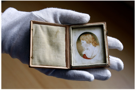 Hand with glove holding a miniature of young Scott