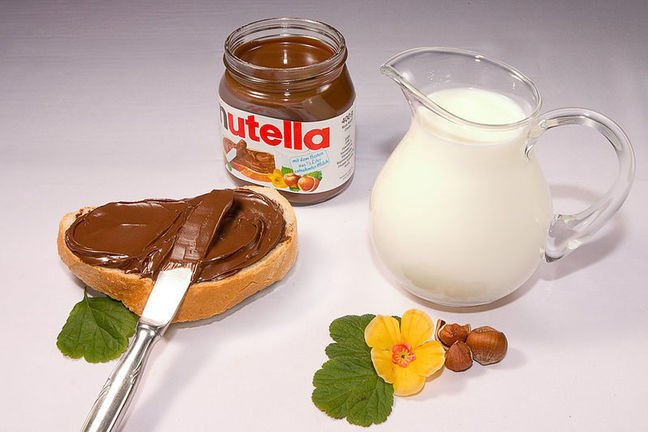 Nutella jar, nutella on bread with knife, glass of milk and hazelnuts.