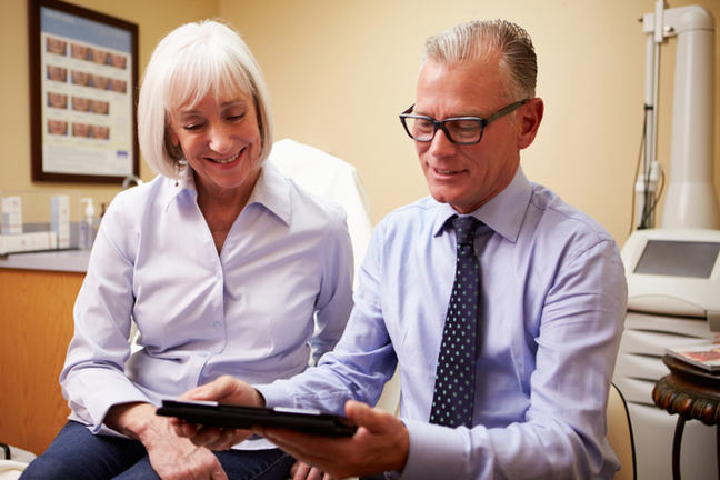 A male doctor showing a tablet computer to a older woman in a consultancy room.
