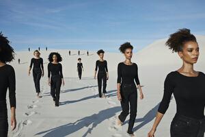 A group of women of different ethnicities walk through a desert landscape