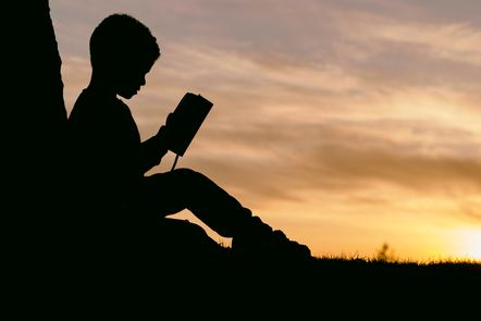 Silhouette of a child reading a book