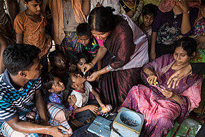 A woman gives oral medicine to a child surrounded by children and adult onlookers