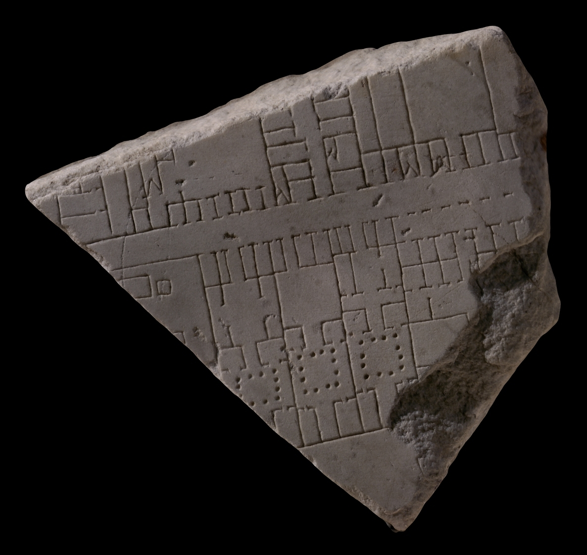 A marble tablet with carvings etched on that consists of lines