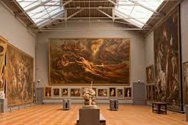 A gallery room from The Royal Museum of Fine Art, Brussels. Several people are in the room, which is large with high ceilings and wooden floors. The walls are covered in various art works, Renaissance in style but indistinguishable from the distance.