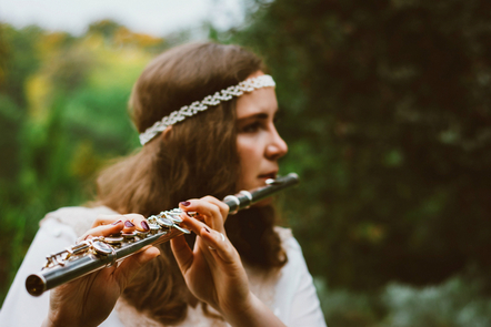 A young woman playing a flute in a forest