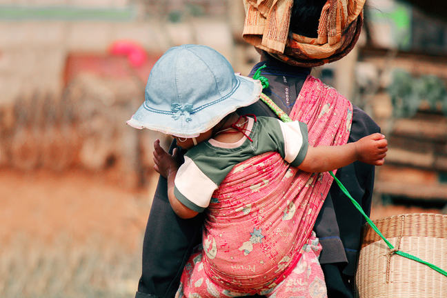 A child on the back of her mother wearing a blue hat.