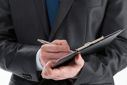 man in business suit writing on a clipboard.