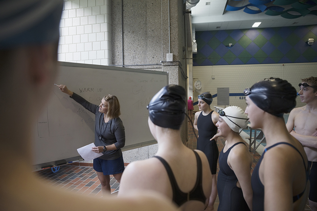 Female coach at whiteboard coaching swimming team at practice