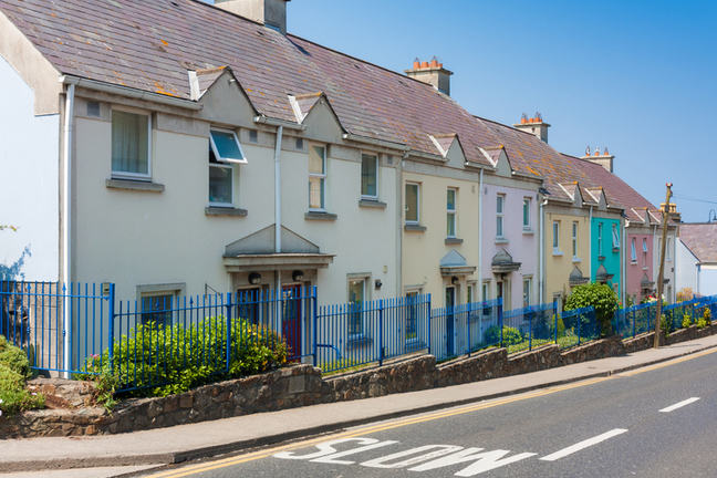 A row of two-storey houses of different colours alongside a road.