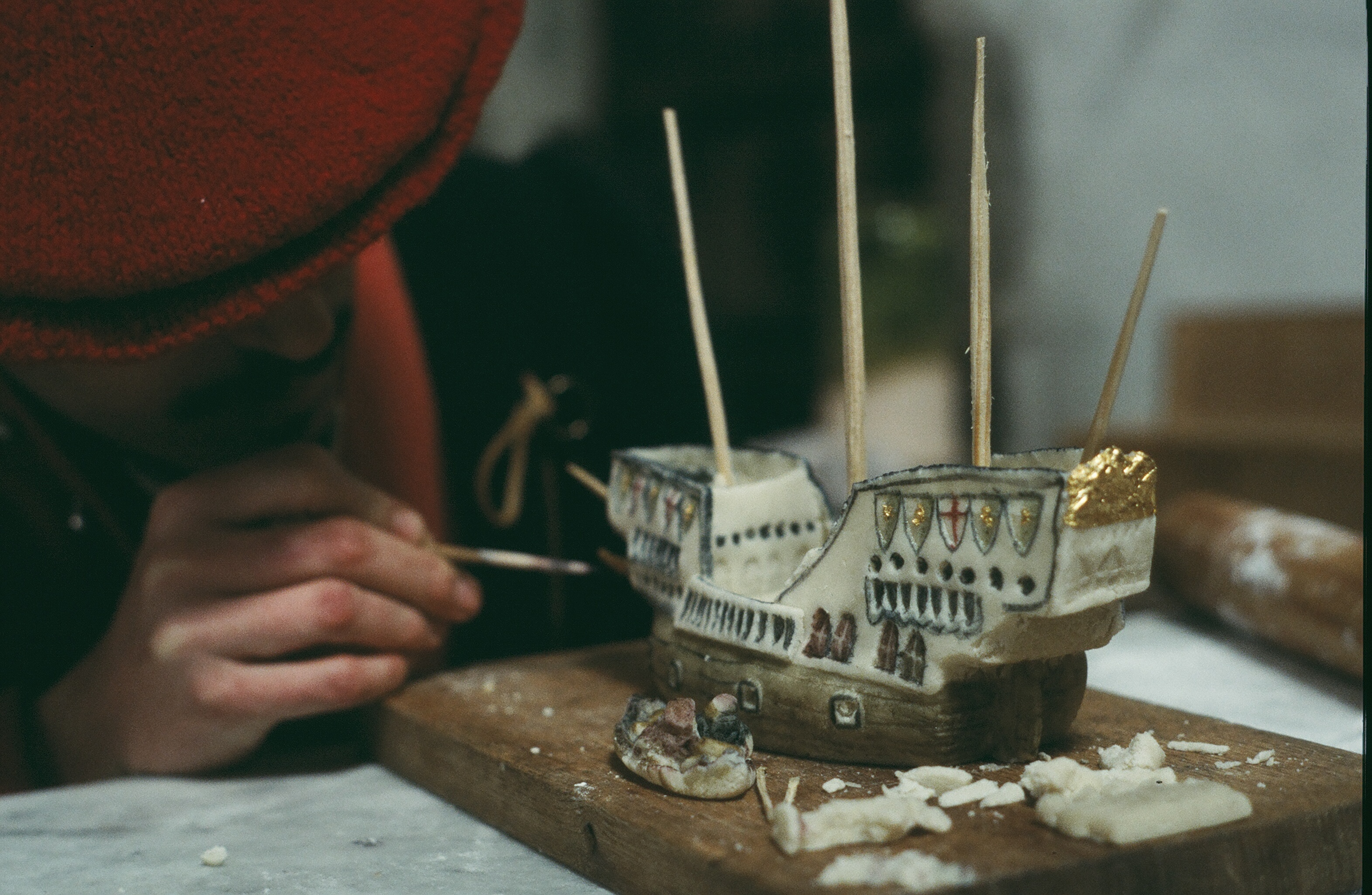 A photograph of a reenactment in a Tudor kitchen, with a cook carefully painting a small ship, made from sugar paste.