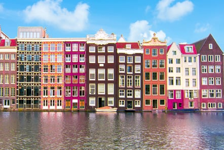 A row of Dutch canal styled houses in Amsterdam overlooking the canal. The buildings are coloured with a range of pink shades, as well as some brown and white.